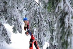 Женщина в платье цвета взбираясь среди деревьев покрыла с снегом Стоковое фото RF