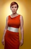 Женщина в померанцовом ретро платье Стоковые Изображения