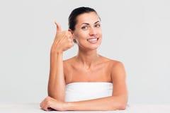 Женщина в полотенце показывая большой палец руки вверх стоковое фото rf