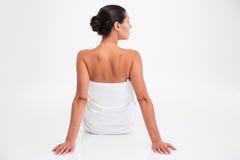 Женщина в полотенце сидя на поле стоковая фотография