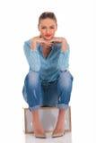 Женщина в представлении джинсовой ткани усаженная с руками на коленях касаясь стороне Стоковые Фото