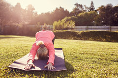 Женщина в представлении йоги на циновку outdoors с sunflare стоковое изображение