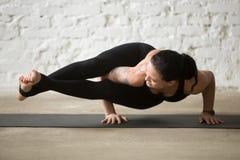 Женщина в представлении Astavakrasana, белый ба молодого yogi привлекательная просторной квартиры Стоковая Фотография RF