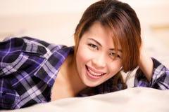 Женщина в пурпуровой рубашке шотландки лежа в кровати стоковое фото
