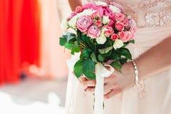 Женщина в платье держа букеты свадьбы роз белизны и biege Стоковое Изображение