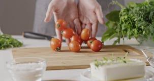 Женщина в рисберме бросая ее руки влажных красных томатов вишни на резать деревянную доску для подготовки салата на белизне сток-видео