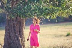 Женщина в розовом платье под оливковым деревом стоковая фотография