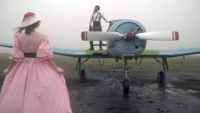 Женщина в розовом платье шестидесятого приходит к винтажному самолету на котором стоит пилот сток-видео