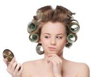 Женщина в ролике волос смотря в зеркале стоковые изображения rf