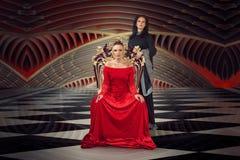Женщина в роскошном платье мантии сидя на троне ферзя стоковые изображения rf