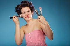 Женщина в роликах волос держит щетки состава Стоковая Фотография RF