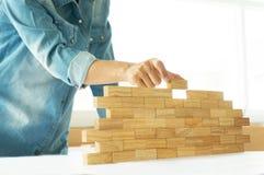 Женщина в рубашке джинсов держа игру древесины блоков стоковое изображение rf