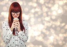 Женщина в рубашке точки польки смотря вниз на кофейной чашке против cream bokeh Стоковое Фото