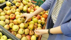 Женщина в рынке плода с яблоком в руке фрукты и овощи много плоды предпосылка магазина естественная здоровая еда стоковая фотография