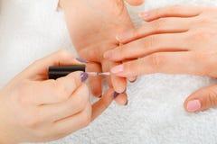 Женщина в салоне красоты получая маникюр сделанный Стоковые Изображения RF