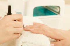 Женщина в салоне красоты получая маникюр сделанный Стоковое Изображение RF
