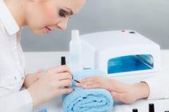 Женщина в салоне красоты получая маникюр сделанный Стоковая Фотография