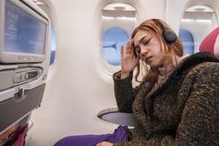 Женщина в самолете страдает от airsick с головной болью стресса во времени полета стоковые фото