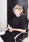 Женщина в салоне красоты, белокурых роликах curlers волос девушки парикмахером. Стиль причёсок. Стоковое Изображение RF