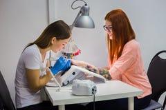 Женщина в салоне ногтя получая маникюр beautician Стоковые Фотографии RF