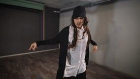 Женщина в свободном времени в студии принимает танцы Она работает бедр-хмель танца движений для девушек бедр-хмель для девушек - акции видеоматериалы