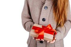 Женщина в связанном свитере держа настоящий момент, подарок упакована в бумаге ремесла с конусами сосны и связана с красной ленто Стоковые Изображения