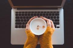 Женщина в сделанном по образцу желтом цвете, шерстяной свитер сидя с компьтер-книжкой стоковые изображения rf