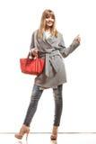Женщина в сером пальто держит красную сумку стоковые фото