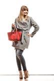 Женщина в сером пальто держит красную сумку стоковое фото