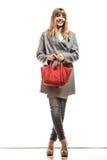 Женщина в сером пальто держит красную сумку стоковые изображения rf