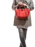 Женщина в сером пальто держит красную сумку стоковое фото rf