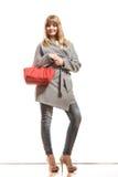 Женщина в сером пальто держит красную сумку стоковое изображение