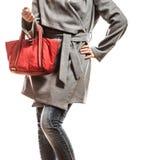 Женщина в сером пальто держит красную сумку стоковые изображения