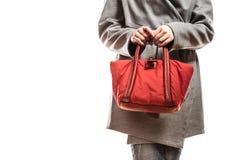 Женщина в сером пальто держит красную сумку стоковая фотография