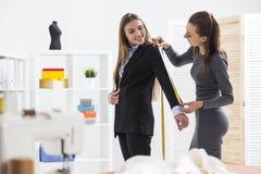 Женщина в сером цвете измеряет ее рукав ` s клиента Стоковое Фото
