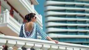 Женщина в солнечных очках наслаждаясь каникулами на летнем дне на балконе кладя руку на античные перила сток-видео