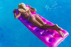Женщина в соломенной шляпе получает suntan на тюфяке воздуха стоковые фото