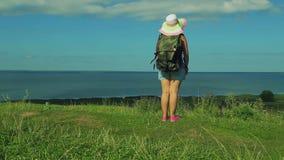 Женщина в соломенной шляпе с рюкзаком за ей назад стоит на крае горы и восхищает природу акции видеоматериалы