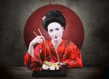 Женщина в составе гейши есть суши стоковые изображения rf
