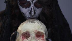 Женщина в составе для торжества Санты Muerte, девушка целует окровавленный череп, конец вверх видеоматериал