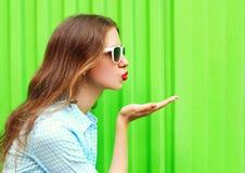 Женщина в солнечных очках посылает поцелуй воздуха над красочным зеленым цветом Стоковые Изображения RF