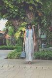 Женщина в солнечных очках с сумкой питона snakeskin моды идя на улицу человека kuta острова bali городок захода солнца формы крас Стоковая Фотография RF