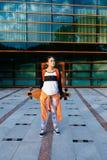 Женщина в солнечных очках с longboard и оранжевой рубашкой внешней Стоковое Изображение