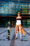 Женщина в солнечных очках с longboard и оранжевой рубашкой outdoors Стоковое Изображение RF