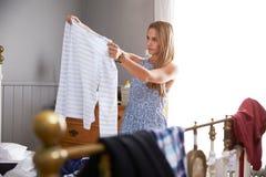 Женщина в спальне выбирая чего нести Стоковое Изображение