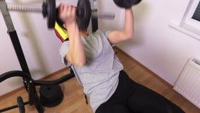 Женщина в спортзале делая тренировки с гантелями сток-видео