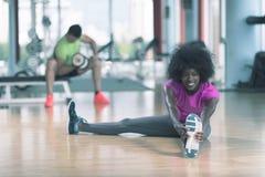 Женщина в спортзале протягивая и нагревая человека в worki предпосылки Стоковое фото RF