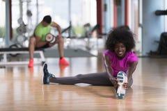 Женщина в спортзале протягивая и нагревая человека в worki предпосылки Стоковое Фото