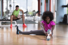 Женщина в спортзале протягивая и нагревая человека в worki предпосылки Стоковые Изображения