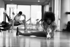 Женщина в спортзале протягивая и нагревая человека в worki предпосылки Стоковые Фото